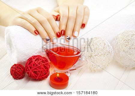 beautiful red manicure with dekor and towel on the white wooden table. spa