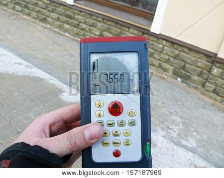 an holding a measuring device for determining the distance.