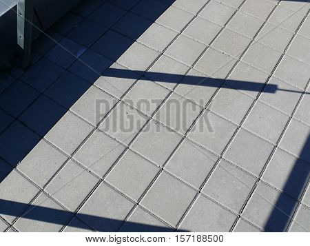 floor roof with square tiles and shadow on railing.