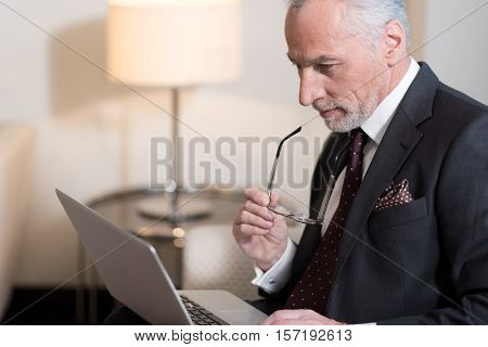Interesting working hours. Involved pleasant bearded businessman holding glasses and sitting in the hotel while working with the laptop