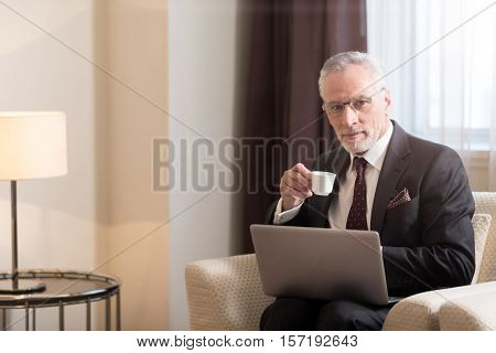Have a break. Pleasant aged bearded businessman holding a cup and drinking coffee while sitting in the hotel in front of the laptop