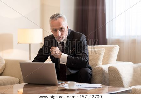Delighted from work. Delighted pleasant bearded businessman sitting in the hotel while working with the laptop and being concentrated