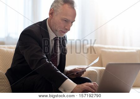 Delighted from work. Smiling delighted bearded businessman sitting in the hotel in front of the laptop and working with papers while expressing interest