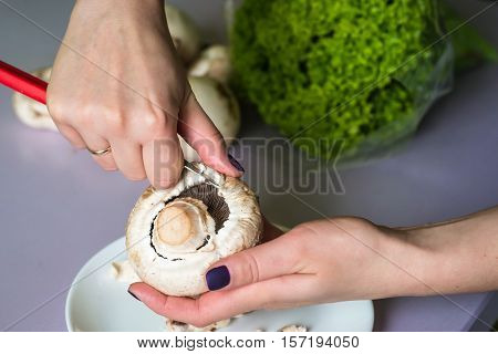 hands clean mushrooms with a knife over a white plate