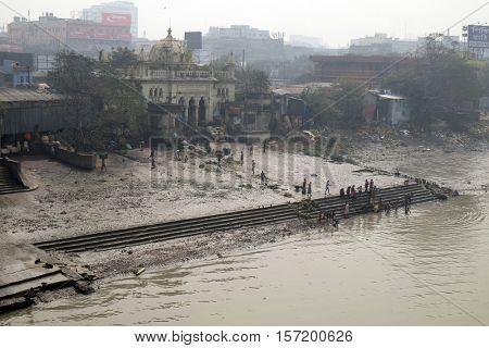 KOLKATA, INDIA - FEBRUARY 10: People bathing in river Hooghly under the busy Howrah bridge in Kolkata on February 10, 2016.