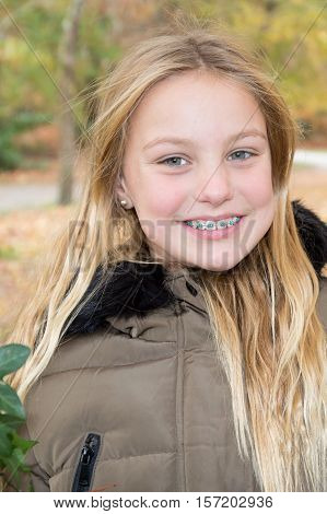 Girl wearing dental braces grinning to show her teeth