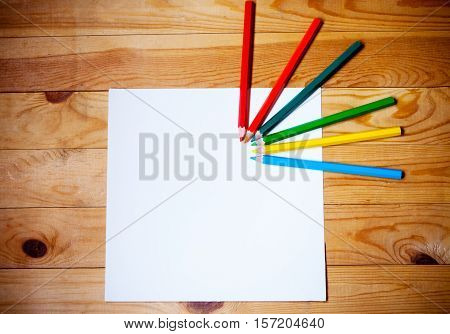 Blank paper and colorful pencils on the wooden background. View from above
