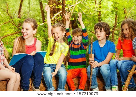 Portrait of happy boys and girls having fun, sitting in a row on the log, in the summer camp