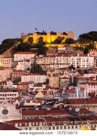Cityscape of Lisbon Portugal with the Sao Jorge Castle seen from Miradouro Sao Pedro de Alcantara at night.
