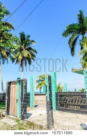 Livingston, Guatemala - August 31 2016: Remains of beachside abandoned demolished building with advertisement sign for Guatemalan Gallo beer painted on wall in Caribbean town of Livingston
