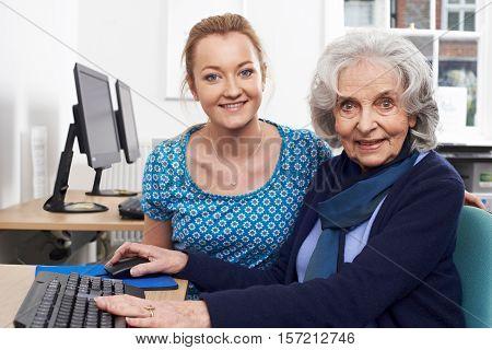Tutor Helping Senior Woman In Computer Class