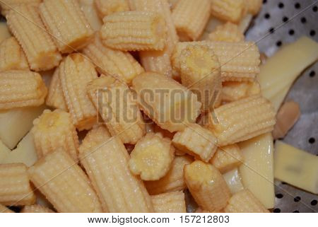 Bits of baby corn and other vegetables in a colander.