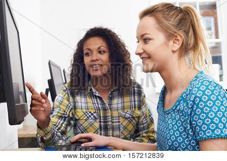 Businesswoman Giving Computer Training To Intern  In Office