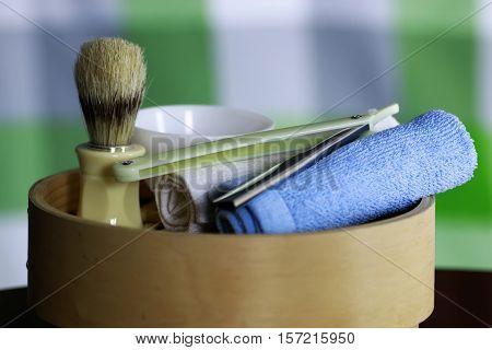 Men's cosmetics shaving brush and straight razor in a wooden basket