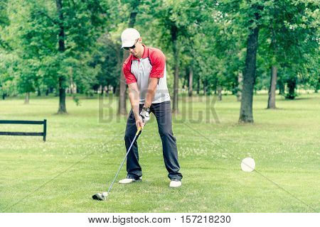 Young golfer teeing off, toned image, outdoors