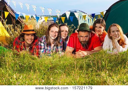 Portrait of six happy friends lying on the grass at campsite on open air festival
