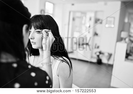 Professional Make- Up Artist Applying Makeup On A Beautiful Brunette Model At Salon Of Beauty. Black