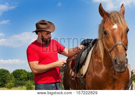 Young man in cowboy hat saddling his chestnut brown horse at sunny summer day