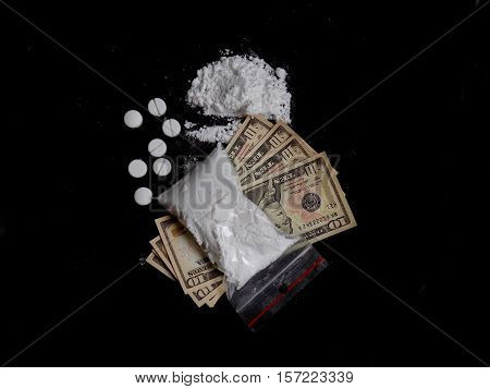 Cocaine drug powder in bag on dollar bills money, pills and cocaine pile on black background