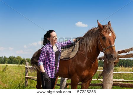 Happy young woman saddling a chestnut brown horse near the enclosure fence in summer