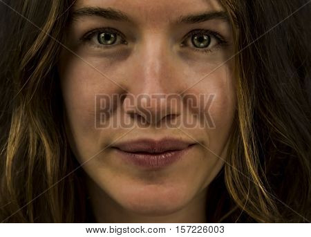 Close up portrait of woman looking straight isolated on black background.