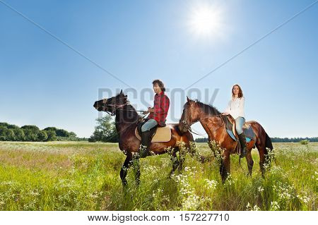 Side view portrait of young happy couple riding bay horses at flowery meadows in summer