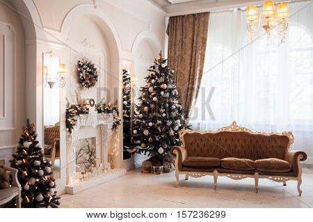 Winter New Year and Christmas decoration in white large living room. Decorated Christmas tree near baroque sofa and classical fireplace in hall.