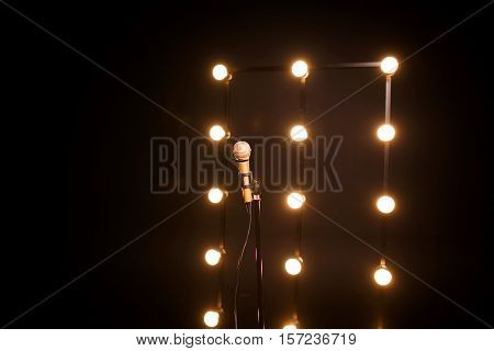 gold microphone on microphone stand on dark background with many lights
