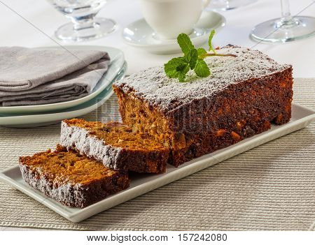 Ginger cake with spices nuts and podered sugar.