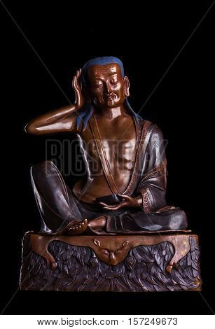 Bronze figure of the famous teacher of Tibetan Buddhism - Milarepa isolated on a black background.