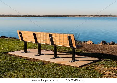 Empty bench at Chula Vista Bayfront Park facing San Diego bay.