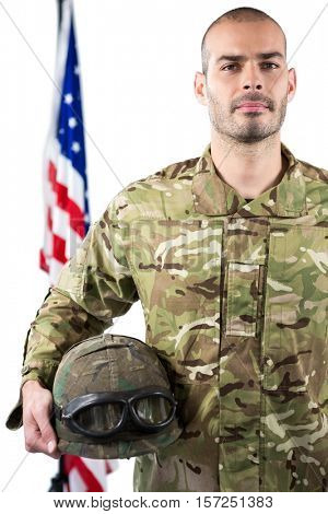 Portrait of smiling soldier standing with combat helmet against white background