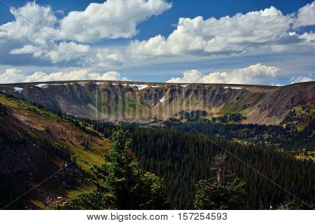 Pine Forest Mountain Ridge with Patches of Unmelted Snow on the Edge of a Bowl in Summer