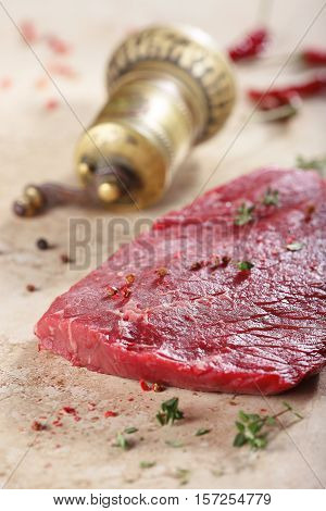 The piece of fresh beef and spises lies on a table-top