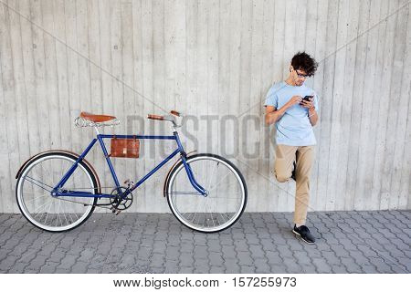 people, communication, technology, leisure and lifestyle - hipster man with smartphone and earphones on fixed gear bike listening to music on city street
