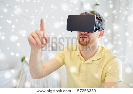 technology, augmented reality, gaming, entertainment and people concept - young man with virtual headset or 3d glasses playing video game over snow