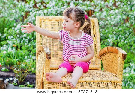 offended little girl is sitting in a wicker chair on the background of blossoming Apple trees