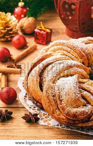 Christmas braided cinnamon roll cake on festive table.