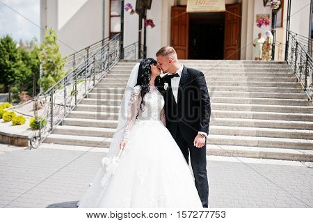 Exuberant Kissed Wedding Couple Near Stairs Of Church.
