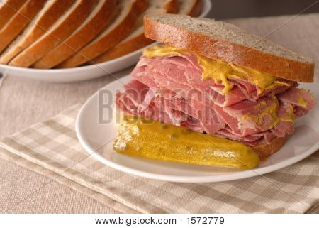 Corned Beef Sandwich With Mustard And Pickle On Rye