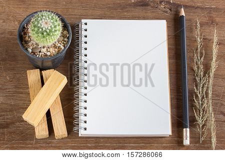 Pencil and notebook on wooden table background with copy space