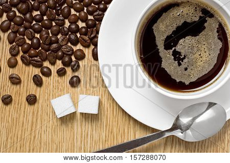 Coffee cup on a table, coffee beans and lump sugar around, studio shot