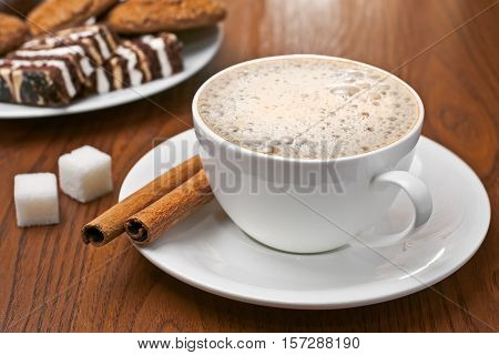Cappuccino with cinnamon bark, lump sugar and plate of sweets on the table