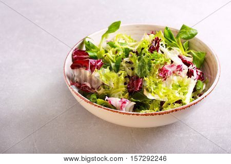 Mix salad leaves and herbs in a bowl over grey background