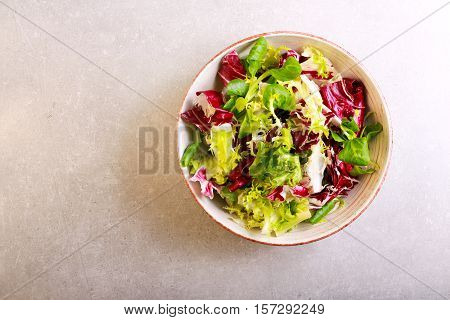 Mix salad leaves and herbs in a bowl over grey background top view