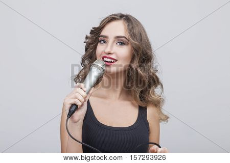 Singing Brown Haired Woman In Gray Room