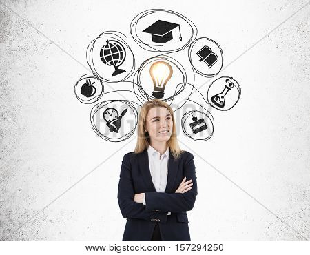 Blond woman with crossed arms is standing near a concrete wall with education sketches and a glowing light bulb