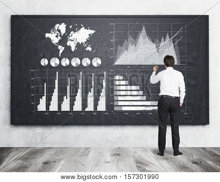 Rear view of a young businessman wearing a white shirt and drawing graphs on large blackboard. Concept of data usage.