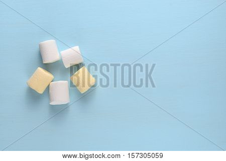 Marshmallow pieces on blue table top view