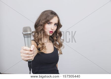 Portrait of young pop star who is giving the microphone to the viewer. Concept of working with the audience. Mock up
